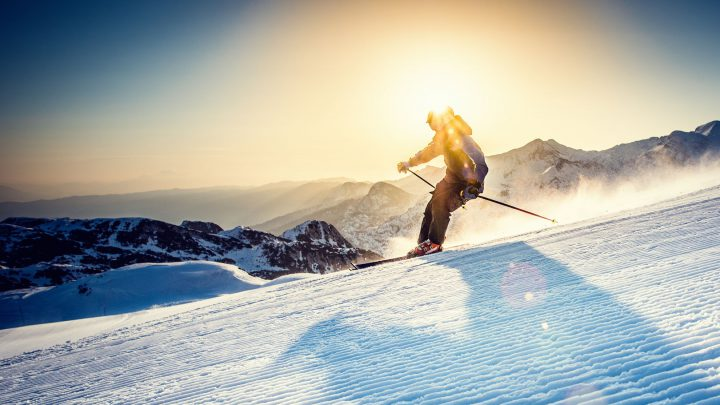 Panoramic shot of young female freestyle skier in high mountains at early morning.