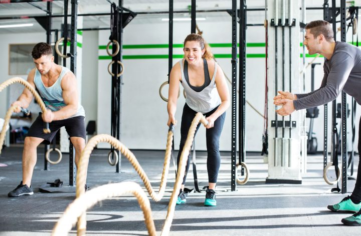 Fitness gym with man and woman working out with battle ropes at the gym with trainer