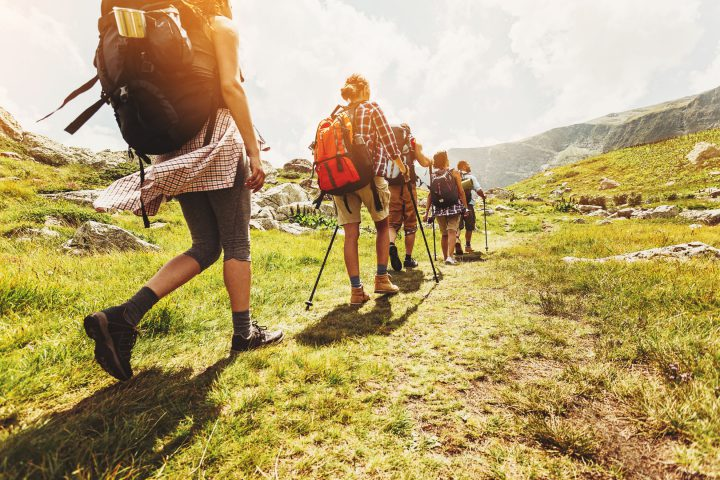 Group of hikers walking in line on a footpath in the mountain, with copy space