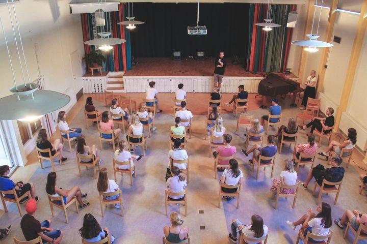 Bild uppifrån i aulan på första samlingen på Hjälmareds konfirmationsläger 2020 med stolar glest uppställda.