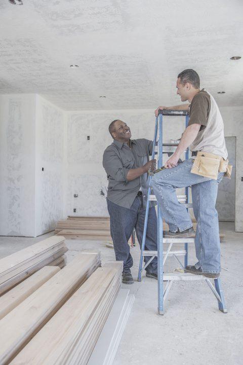 Två killar som pratar i ett hus under uppbyggnad.